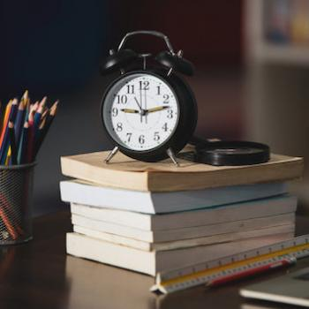 Ticking clock on school books.