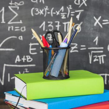 Books, pencils, scissors in front of a chalkboard with math equations.