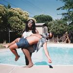 a person carrying a man out of a pool
