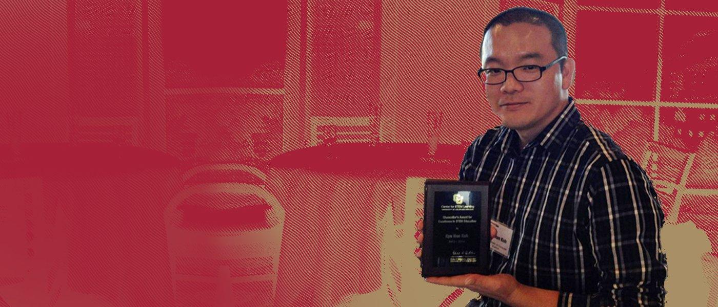 Assistant Professor Kyu Han Koh holding the award