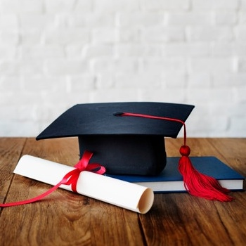 Photo of mortarboard, books and degree.