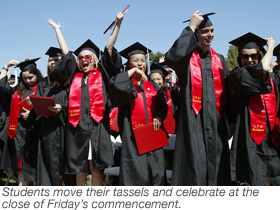 Students move their tassels and celebrate at the close of Friday's commencement.